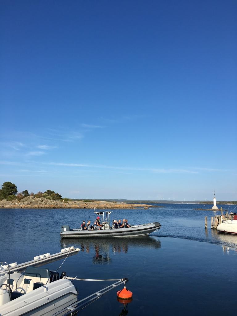 Ribbåten lämnar hamnen. kvar på kajen står familj och support.Nästa gång vi ses är vid simuppgången.